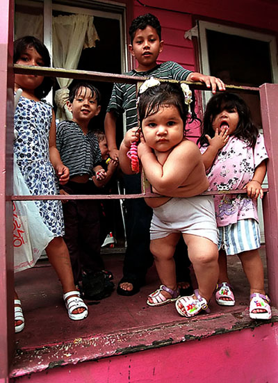 Children gather on the front porch of a home on Houston Street in the West Mannheim community of Franklin Park, Ill.  West Mannheim is an overcrowded, largely Latino section of the suburb.