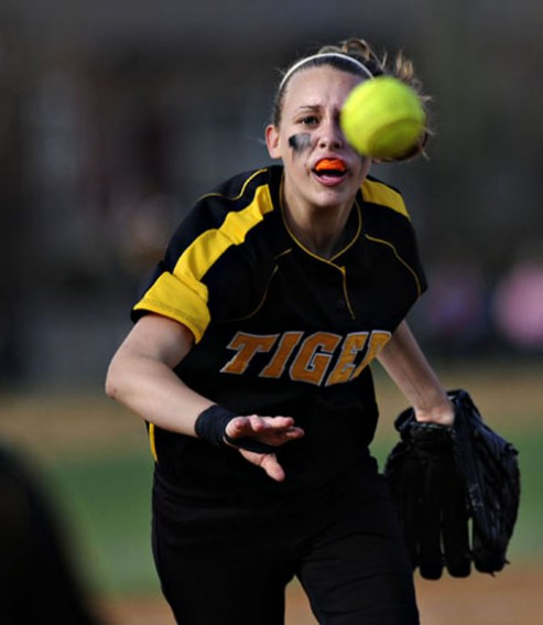 Elmwood Park High School's Katelyn Jakobsen throws the ball to first base during a game against Resurrection.