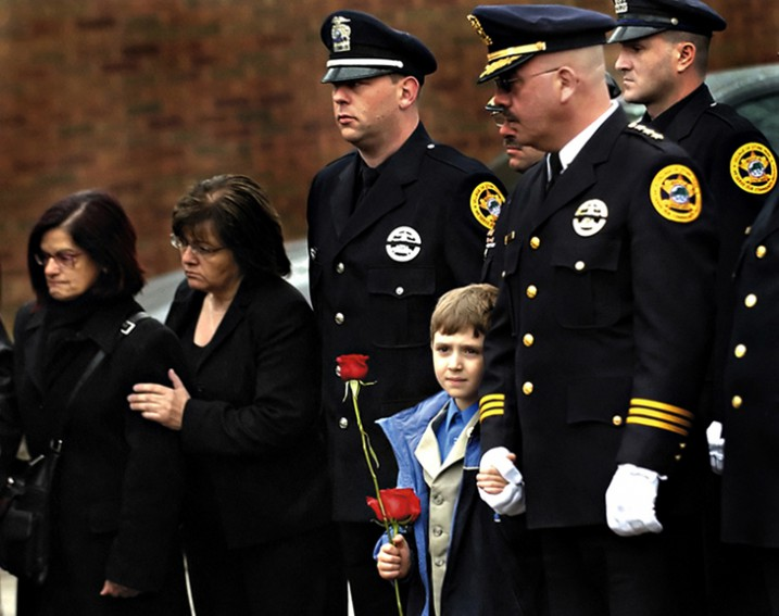 A Stone Park police officer holds hands with Luciano Mazzulla, the son of late Police Officer Ivano Mazzulla. Mazzulla's funeral was held at Our Lady of Mount Carmel Church in Melrose Park, Ill.